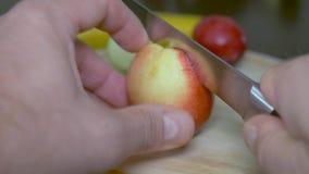 Zoete verse mooie nectarine De man snijdt het in twee gelijke delen Close-up, op een houten achtergrond stock videobeelden
