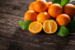 Zoete verse sinaasappelen en de helft van sinaasappel op houten Stock Foto