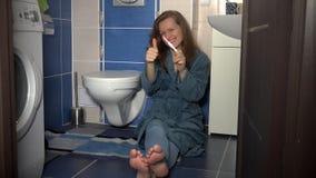 Zoete vrouwenzitting op badkamersvloer die positieve zwangerschapstest tonen aan camera stock footage