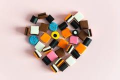 Zoethoutallsorts Snoepjes in hartvorm op roze achtergrond De ruimte van het exemplaar stock foto's