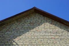 Zolder van een baksteenhuis tegen een blauwe hemel stock afbeeldingen