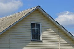Zolder van een grijs huis met een klein venster tegen een blauwe hemel royalty-vrije stock afbeelding