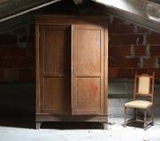 zolder van het huis met een houten garderobe en een oude bouwvallige stoel royalty-vrije stock fotografie