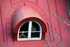 Zoldervenster op het rode dak van de oude stad stock foto