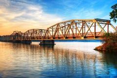 Zoll-Brücke über Fluss am Sonnenaufgang stockfoto