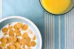 Zolla di cereale da prima colazione e di vetro del succo di arancia sulla tabella-clotch Fotografie Stock Libere da Diritti