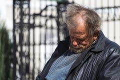 Zolochiv, Украина - 10-ое апреля 2018: Бездомный сидеть бродяги уснувший Стоковые Изображения