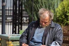 Zolochiv, Украина - 10-ое апреля 2018: Бездомный сидеть бродяги уснувший Стоковое Изображение RF