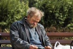 Zolochiv, Украина - 10-ое апреля 2018: Бездомный сидеть бродяги уснувший Стоковые Фотографии RF