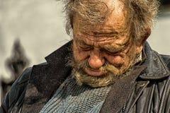Zolochiv, Украина - 10-ое апреля 2018: Бездомный сидеть бродяги уснувший Стоковая Фотография