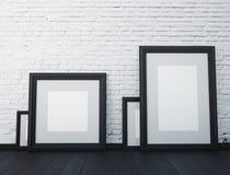 Zombaria acima do quadro quadros pretos na parede branca no interior Foto de Stock Royalty Free