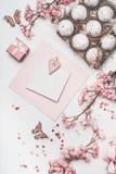 Zombaria bonita do cartão da Páscoa do rosa pastel acima com decoração da flor, corações, ovos na caixa da caixa na mesa branca fotografia de stock