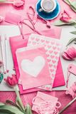 Zombaria bonita do rosa acima com tulipas, pacote de papel com corações, pena de marcador, etiquetas e xícara de café no desktop  Fotos de Stock Royalty Free