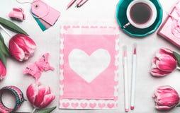 Zombaria consideravelmente cor-de-rosa acima com tulipas, pacote de papel com corações, pena de marcador, etiquetas e xícara de c Foto de Stock Royalty Free
