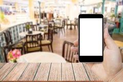 Zombe acima da imagem da mão que guarda o telefone celular preto com a tela branca vazia Fotos de Stock