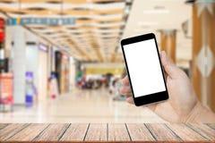 Zombe acima da imagem da mão que guarda o telefone celular preto com a tela branca vazia Foto de Stock