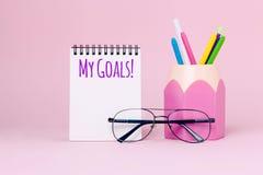 Zombe acima da imagem do caderno e dos materiais de escritório, suporte do lápis no fundo cor-de-rosa imagens de stock