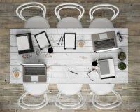 Zombe acima da tabela de conferência da reunião com acessórios do escritório e laptop, fundo interior do moderno, Foto de Stock