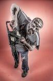 Zombi con la sierra mecánica Imagenes de archivo