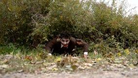 Zombi ensanglanté rampant au sol banque de vidéos