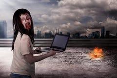 Zombi féminin rampant dactylographiant avec l'ordinateur portable photographie stock