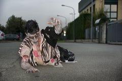 Zombi masculin rampant sur ses genoux, sur la rue vide de ville Images stock