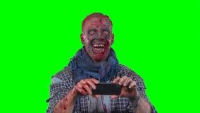 Zombi masculino que usa el teléfono celular almacen de video