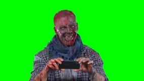 Zombi masculino que usa el teléfono celular metrajes