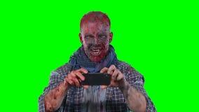 Zombi masculino que usa el teléfono celular almacen de metraje de vídeo