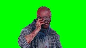 Zombi masculino que usa el teléfono celular que llama alguien metrajes