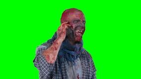 Zombi masculino que usa el teléfono celular que llama alguien almacen de metraje de vídeo