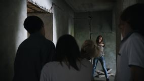 A zombie apocalypse. Survived woman with a gun walking out from the wall and aiming in the zombies