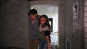 A zombie attack in abandoned building. Tired survivors holding by each other and escaping from the zombies in daylight