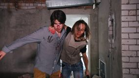 A zombie attack in abandoned building. Tired survivors holding by each other and escaping from the zombies
