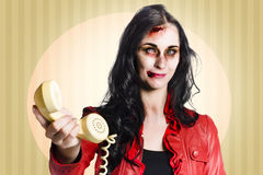 Zombie business person handing over bad news phone. Grunge portrait of a evil demon business woman handing over retro telephone reciever when giving bad news Royalty Free Stock Photo
