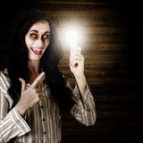 Zombie girl holding lightbulb with bad idea. Zombie business person standing in a dimly lit attic holding an illuminated lightbulb in a depiction of a bad idea Stock Photo