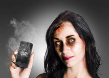 Zombie business woman holding dead technology. Zombie business girl with bloodshot eyes holding smoking mobile phone with skull and crossbones in a depiction of Stock Photos