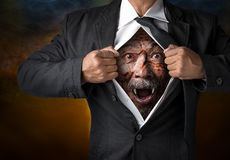 Zombie businessman. Zombie face inside the businessman body in concept of wicked business Royalty Free Stock Photography