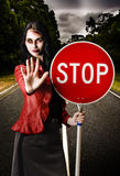 Zombie girl holding stop sign at dead end. Zombie businesswoman halting traffic on a dreary road while holding a stop sign in a dead end concept Royalty Free Stock Images