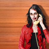 Zombie call centre worker cold calling on phone. Dead call centre worker holding office telephone while startling customers in a depiction of cold calling Stock Photography