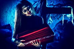 Zombie child. Bloodthirsty witch standing at the night cemetery and holding a coffin Stock Photo
