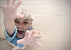 Zombie child boy screaming and reaching hand. Through hole on cardboard. Halloween day concept. Copy space Royalty Free Stock Image