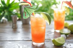 Zombie Cocktail. With Rum, garnished with lime. Cold sweet summer fruit red alcohol cocktail, refreshing drink on wooden table, copy space royalty free stock photography