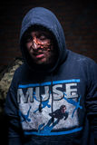 Zombie with disfigured face and dirty clothes Stock Photos