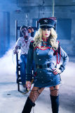 Zombie Experiment. A women dressed like a military officer with a zombie in her background Stock Images