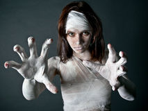 Zombie girl. Girl in jeans, bandages, and a hat standing on a black background Stock Images