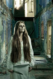 Zombie girl in abandoned building. With knife Stock Photo