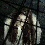 Zombie girl behind lattice. Looking into camera Stock Image