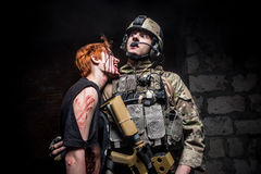 Zombie Girl biting a soldier Stock Photography