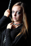 Zombie girl with black tears and cut throat clings metal chain royalty free stock photo